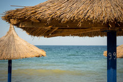 Wooden umbrellas on the beach in Romania.  royalty free stock images