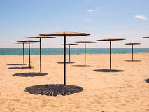 Wooden umbrellas on an empty beach Royalty Free Stock Images