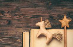Wooden unicorn and wooden wand on beige shabby sheets. Old torn books. Soft light. Teal orange toning. Imagination concept. royalty free stock photo