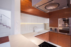 Wooden units in kitchen. Wooden units with granitic white wheat in stylish kitchen stock photography