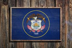 Wooden Utah flag. 3d rendering of an Utah State USA flag on a wooden frame and a wood wall Stock Image