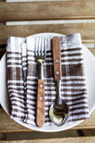 Wooden Utensils on white plate with kitchen towel Royalty Free Stock Photo