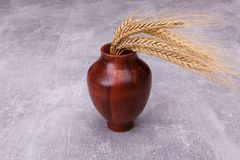 A wooden vase with wheat ears stock photos
