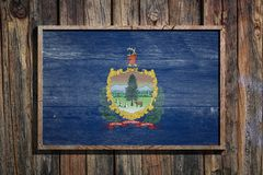 Wooden Vermont flag. 3d rendering of a Vermont State USA flag on a wooden frame and a wood wall Stock Images