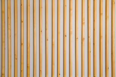 Wooden vertical slats batten on a light gray wall background. Interior detail, texture, background. The concept of minimalism and stock photos