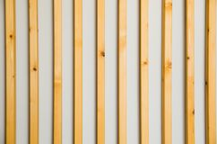 Wooden vertical slats batten on a light gray wall background. Interior detail, texture, background. The concept of minimalism and stock photo