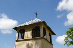 Wooden village bell tower on blue sky background. Old wooden village church bell tower on blue spring sky background Stock Photography