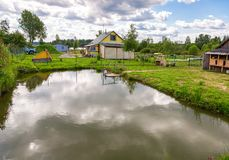 Wooden village house with outbuildings and small pond Stock Photo