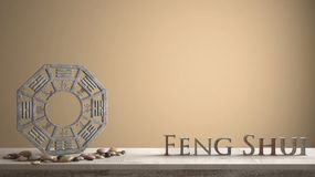 Wooden vintage table shelf with ba gua and 3d letters making the word feng shui with orange brown background with copy space, zen. Concept interior design royalty free stock photography