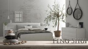Wooden vintage table shelf with pebble balance and 3d letters making the word feng shui over blurred bedroom with window, chest of. Drawer and big olive tree royalty free stock photo
