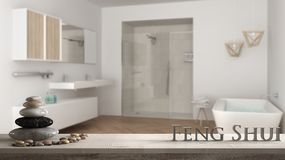Wooden vintage table shelf with pebble balance and 3d letters making the word feng shui over blurred bright bathroom with double s. Ink, shower and bathtub, zen stock photo