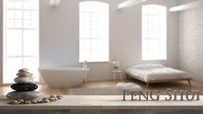 Wooden vintage table shelf with pebble balance and 3d letters making the word feng shui over blurred industrial bedroom with big w. Indows, brick wall, zen stock images