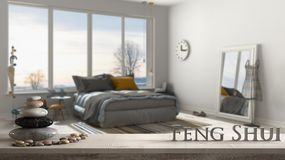 Wooden vintage table shelf with pebble balance and 3d letters making the word feng shui over blurred modern colored bedroom with b. Ig panoramic window, zen royalty free stock photos