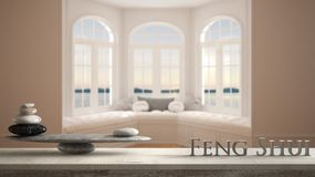 Wooden vintage table shelf with stone balance and 3d letters making the word feng shui over big window with sea panorama, minimali. St empty space, zen concept royalty free stock photos