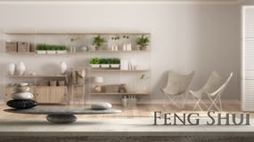 Wooden vintage table shelf with stone balance and 3d letters making the word feng shui over wooden bookshelf, vertical garden stor. Age shelving, living room royalty free stock photography