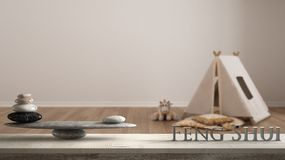 Wooden vintage table shelf with stone balance and 3d letters making the word feng shui over empty room with tent, blanket pillow a. Nd toy on parquet flooring stock photos