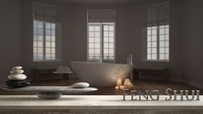 Wooden vintage table shelf with stone balance and 3d letters making the word feng shui over hotel spa bathroom with bathtub, night. Scene, zen concept interior stock photography