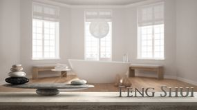 Wooden vintage table shelf with stone balance and 3d letters making the word feng shui over hotel spa bathroom with bathtub, zen c. Oncept interior design stock photo