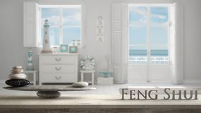 Wooden vintage table shelf with stone balance and 3d letters making the word feng shui over Mediterranean white living, windows wi. Th sea panorama, zen concept stock photography