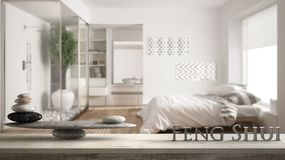 Wooden vintage table shelf with stone balance and 3d letters making the word feng shui over minimalist bedroom and bathroom with s stock photos