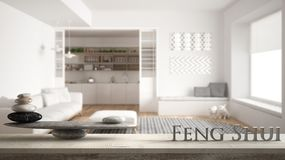 Wooden vintage table shelf with stone balance and 3d letters making the word feng shui over minimalist living room with sofa and b. Ig round carpet, zen concept stock images