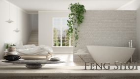 Wooden vintage table shelf with stone balance and 3d letters making the word feng shui over scandinavian bedroom with bathtub, zen. Concept interior design stock image