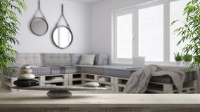 Wooden vintage table or shelf with stone balance, over blurred diy living room with pallet handmade sofa, feng shui, zen concept a. Rchitecture interior design royalty free stock images