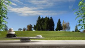 Wooden vintage table or shelf with stone balance, over blurred meadow with grass and blue sky, feng shui, zen concept architecture. Interior design stock images