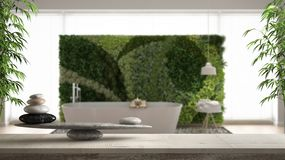 Wooden vintage table or shelf with stone balance, over blurred modern bathroom with bathtub and vertical garden, feng shui, zen co. Ncept architecture interior stock photography