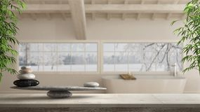Wooden vintage table or shelf with stone balance, over blurred scandinavian bathroom with panoramic window, feng shui, zen concept stock images