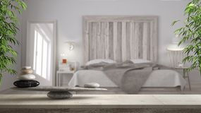 Wooden vintage table or shelf with stone balance, over blurred scandinavian bedroom wooden headboard, feng shui, zen concept archi. Tecture interior design stock image