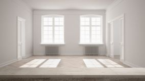 Wooden vintage table top or shelf closeup, zen mood, over blurred empty room with parquet floor, big windows, doors and radiators,. White architecture interior royalty free stock image