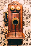 Wooden Vintage Telephone on the wall. Selective focus on speaker and blurred phone Royalty Free Stock Images