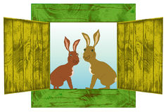 Wooden vintage window with two Easter rabbits. Open cracked window with shutters and rabbits Stock Image