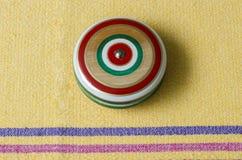 Wooden vintage yoyo on yellow tablecloth. Traditional mexican toy on yellow tablecloth made in Oaxaca, Mexico