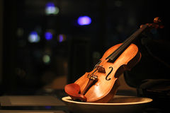 Wooden violin with dark background. Nice looking wooden violin on the table after the show Stock Image