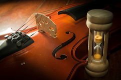 Wooden violin with hourglass. Royalty Free Stock Photos