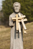 Wooden votive crucifixes on wooden statue. Royalty Free Stock Photo
