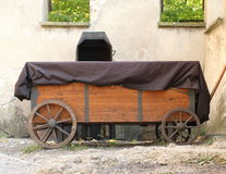 Wooden Wagon. Brown wooden wagon with round wooden wheels parked by the fence Royalty Free Stock Images