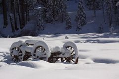 Wooden wagon covered with snow. An old fashion wooden wagen sitting in a field covered with snow Stock Image