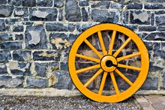 Wooden Wagon Wheel. An old yellow wooden wagon wheel leaning against a stone wall Stock Image