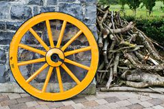 Wooden Wagon Wheel. An old antique yellow wooden wagon wheel leaning against a stone wall Royalty Free Stock Photos