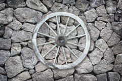 Wooden wagon wheel on a stone back ground. Royalty Free Stock Image