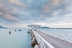 Wooden walk way leading to sea with cloudy sky Royalty Free Stock Images
