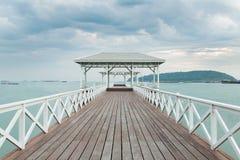 Wooden walk way leading to white pavilion Stock Photo