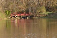 Wooden walking bridge across lake. Wooden walking foot bridge across lake, local  park Royalty Free Stock Photography