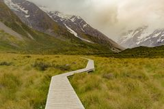 Wooden walking path leading to Hooker valley track. New Zealand natural landscape background Royalty Free Stock Photo