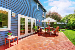 Wooden walkout deck in the backyard garden of blue siding house. Royalty Free Stock Photo