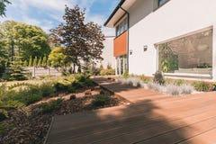 Wooden walkout deck in garden. Exterior of exclusive house with wooden walkout deck in garden stock images