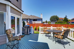 Wooden walkout deck with patio table set and barbecue Stock Photo